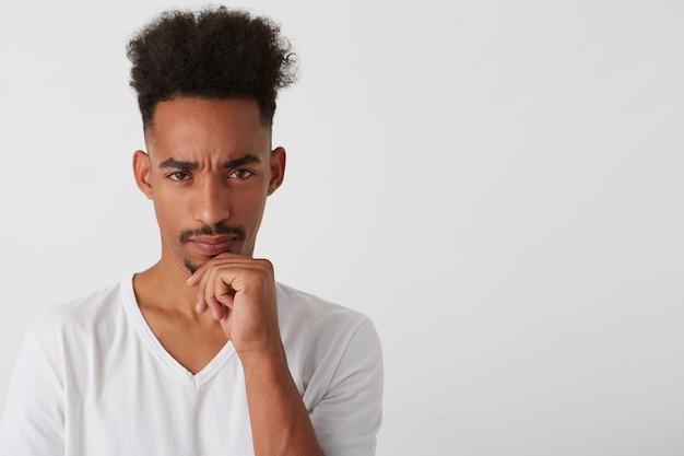 Ritratto di giovane uomo barbuto abbastanza mora con la pelle scura che tiene il mento