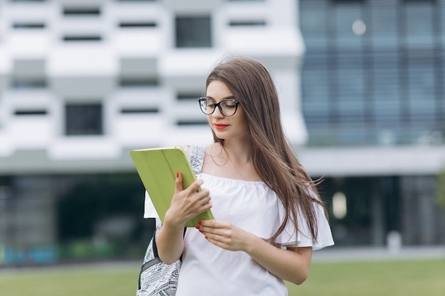 Portrait young pretty businesswoman using tablet device while standing outdoors big urban building