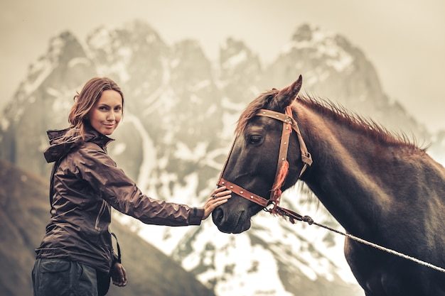 Portrait of young pretty cheerful woman with horse