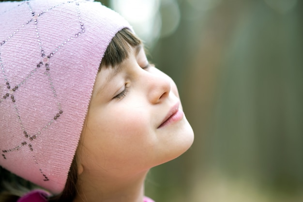Portrait of young pretty child girl wearing pink jacket and cap enjoying warm sunny day in early spring outdoors.