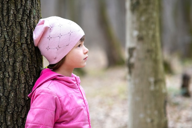 Portrait of young pretty child girl wearing pink jacket and cap leaning to a tree in forest enjoying warm sunny day in early spring outdoors.