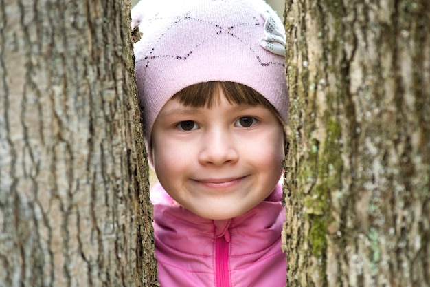 Portrait of young pretty child girl wearing pink jacket and cap standing between trees