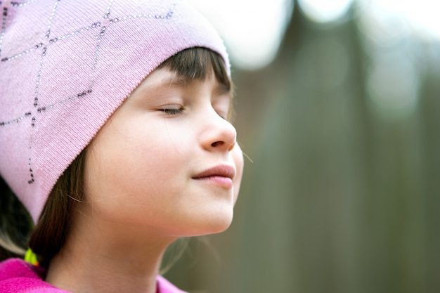 Portrait of young pretty child girl wearing pink jacket and cap