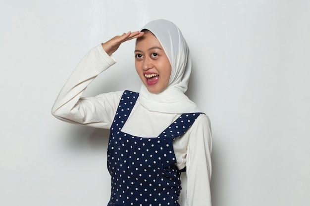 Portrait of young pretty curious muslim woman peeking through her fingers like binoculars