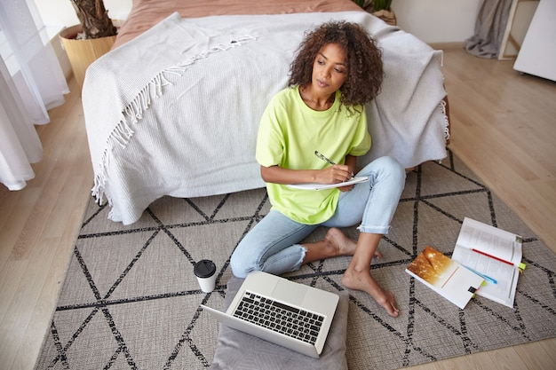 Ritratto di giovane donna dalla pelle piuttosto scura che si siede sul tappeto con libri e laptop moderno, prendendo appunti e guardando attentamente da parte, indossando abiti casual