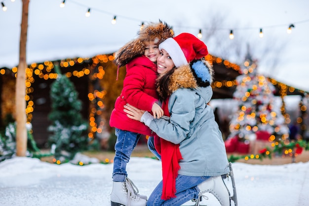 Portrait of young pretty girl in traditional russian fur cap with ear flaps and red winter jacket and white skates posing with her mom on the ice rink against christmas background.