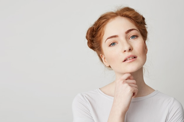 Portrait of young pretty girl with red hair touching chin .