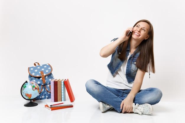 Ritratto di giovane studentessa ridente che parla al telefono cellulare guardando in alto seduto vicino al globo, zaino, libri scolastici isolati