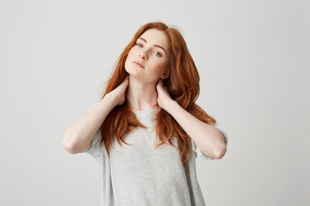 Portrait of young pretty redhead girl touching neck .