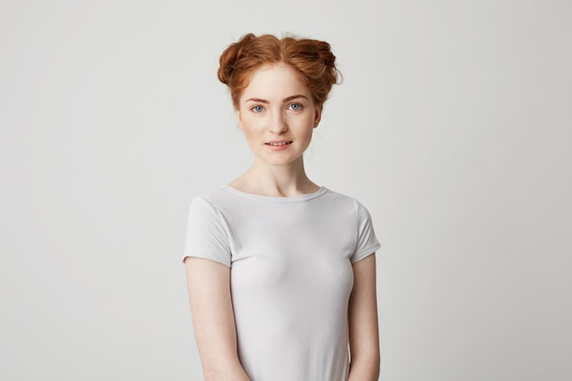 Portrait of young pretty redhead girl with buns smiling .