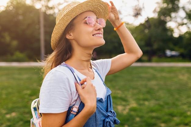 Ritratto di giovane donna abbastanza sorridente in cappello di paglia e occhiali da sole rosa che cammina nel parco, stile di moda estiva, vestito colorato hipster