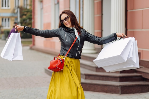 Portrait of young pretty stylish girl holding the shopping bags and looking forward in a good mood. ideal shopping.