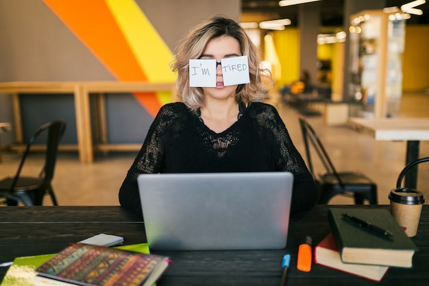 Portrait of young pretty tired woman with paper stickers on glasses sitting at table in black shirt working on laptop in co-working office, funny face expression, frustrated emotion