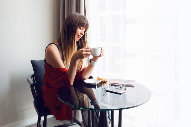 Ritratto di giovane donna graziosa che beve caffè, facendo colazione a casa la mattina