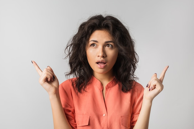 Portrait of young pretty woman, mixed race, curly hair, suprised, shocked emotion on face, , isolated, orange blouse, big eyes, open mouth, pointing fingers up, thinking about choise