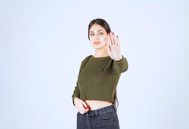 Ritratto di un modello di giovane donna graziosa in piedi e facendo il segnale di stop.
