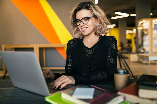 Ritratto di giovane bella donna seduta al tavolo in camicia nera, lavorando sul portatile in ufficio di co-working, con gli occhiali, sorridente, occupato, fiducioso, concentrazione, studente in classe