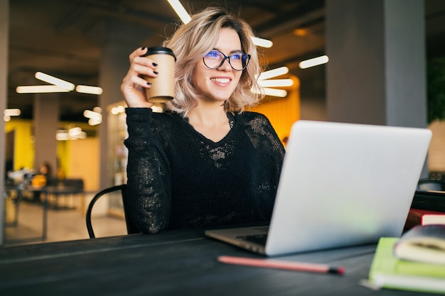 Portrait of young pretty woman sitting at table in black shirt working on laptop in co-working office