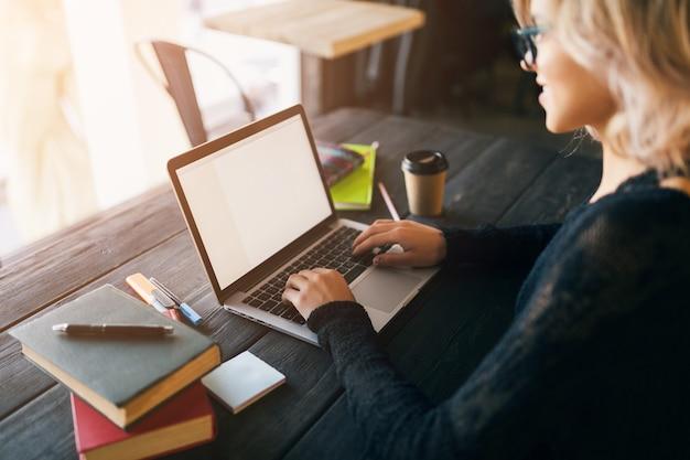 Ritratto di giovane donna graziosa che si siede al tavolo in camicia nera che lavora al computer portatile in ufficio di co-working
