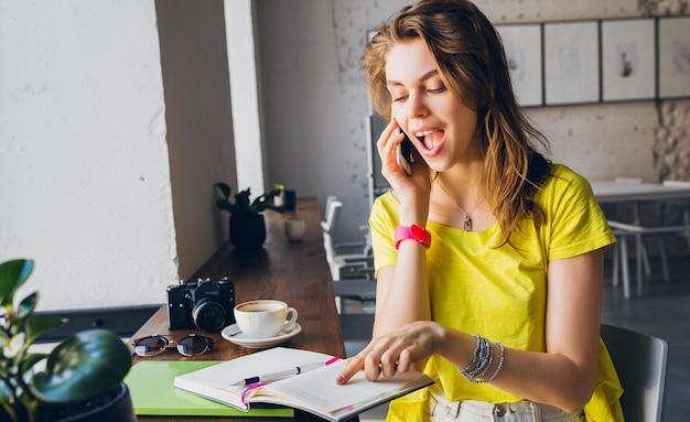 Ritratto di giovane donna graziosa seduta a tavola, apprendimento degli studenti, educazione, stile hipster estivo, sorridente, con in mano libri, parlando al telefono intelligente, uscito