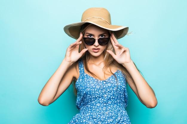 Ritratto di giovane donna graziosa in cappello estivo e occhiali da sole isolati su sfondo blu