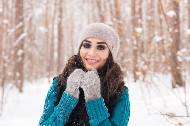Portrait of young pretty woman walking in the winter snowy park at sunny day