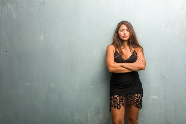 Portrait of young pretty woman wearing a dress against a wall very angry and upset, very tense, screaming furious, negative and crazy