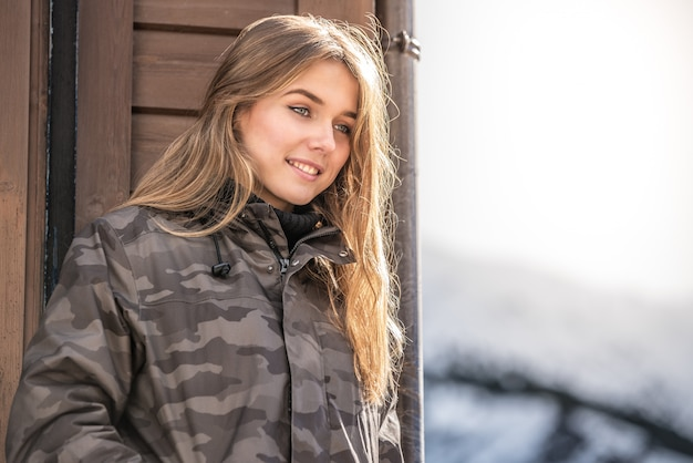 Portrait young pretty woman in winter in a log cabin in the snow