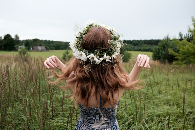 Portrait of young pretty woman with circlet of camomile flowers on head