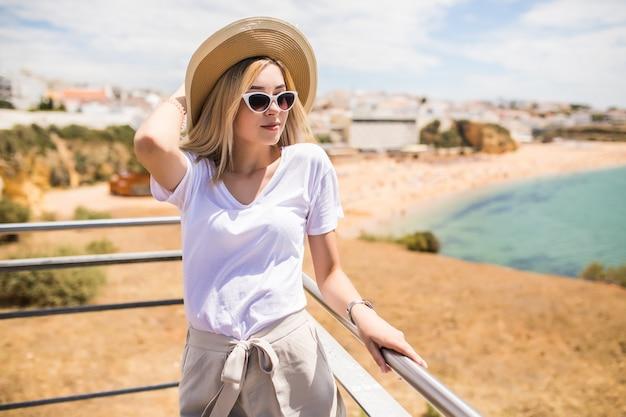 Ritratto di giovane donna graziosa con cappello e occhiali da sole in alto vicino alla spiaggia