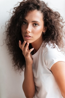 Portrait of a young pretty woman with long curly hair