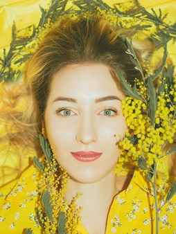 Portrait of young pretty woman with mimosa on the yellow background closeup