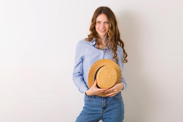 Ritratto di giovane donna graziosa con camicia di cotone blu jeans cappello di paglia in posa sul muro bianco