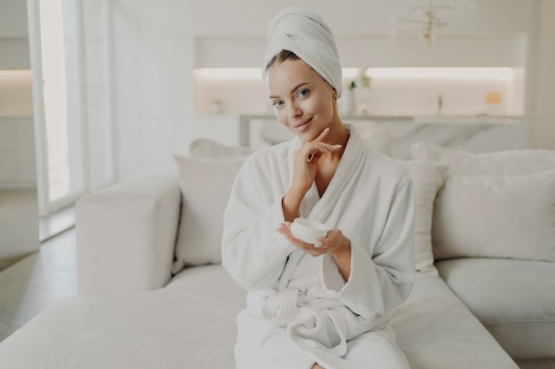 Portrait of young pretty woman with in white bathrobe and towel on head holding cosmetic cream, touching her soft healthy face skin and smiling while relaxing on sofa in cozy apartment