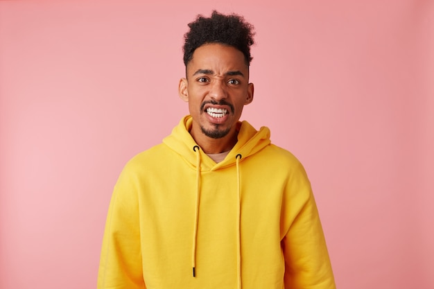 Portrait of young querulous african american guy in yellow hoodie, frowningin and misunderstanding of what is happening,ugly looking.