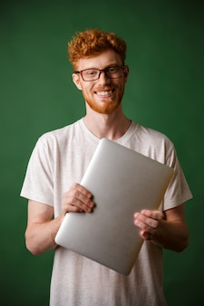 A portrait of young readhead bearded man in white tshirt holding laptop