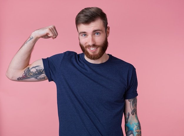 Portrait of young red-bearded handsome manful guy demonstrates biceps and strength, pleased with himmself, broadly smiling and looking at the camera isolated over pink background.
