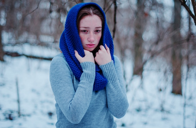 Portrait of young red hair girl with freckles wearing at blue knitted wool scarf in winter day.