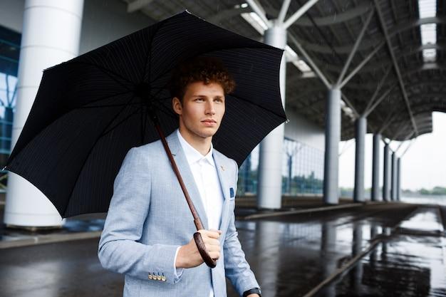 Ritratto di giovane uomo d'affari dai capelli rossi che tiene ombrello nero in strada piovosa