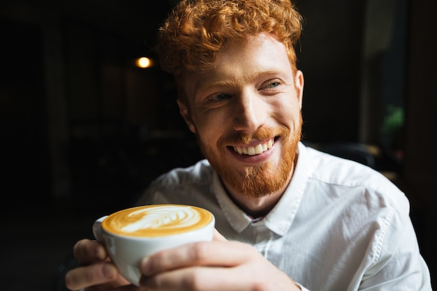 Portrait of young redhead bearded man with charming smile in white shirt holding coffee cup, looking aside