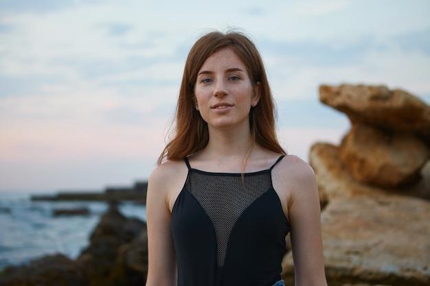 Ritratto di giovane signora carina rossa con le lentiggini sulla spiaggia, guarda la telecamera e sorride, sembra positivo e felice.