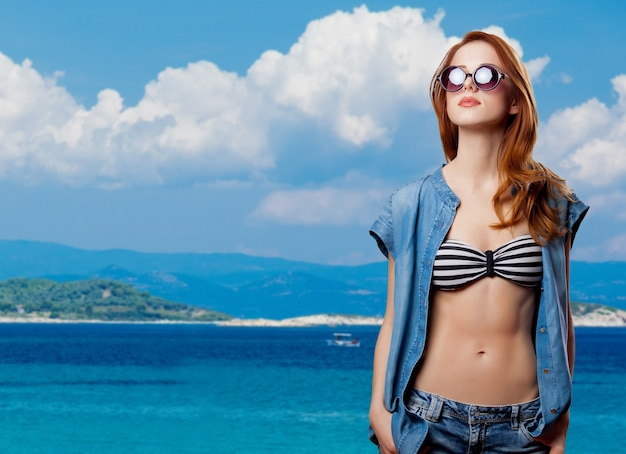 Portrait of a young redhead girl in bikini and sunglasses on tropical summer