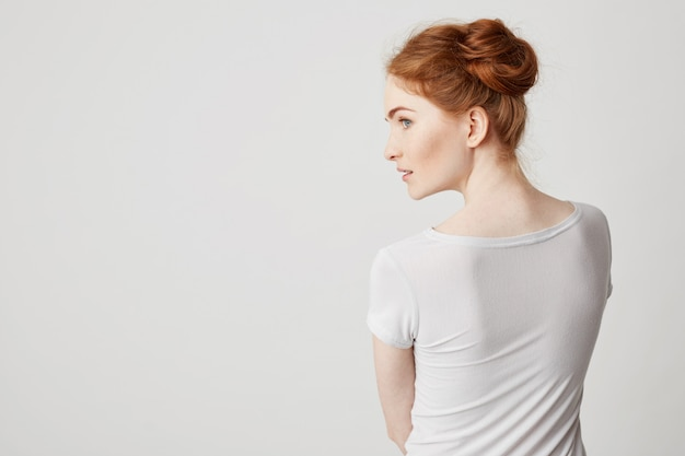 Portrait of young redhead girl with buns standing back to camera looking in side .