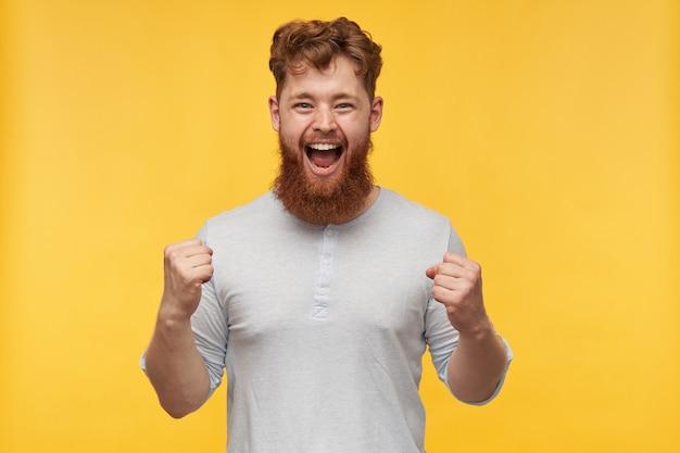 Ritratto di giovane uomo gioioso rossa con una folta barba, sorride ampiamente e mostra i suoi muscoli in giallo