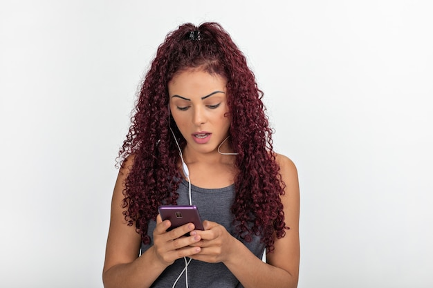 Portrait of a young redhead using cellphone with headphones, surprised and looking at the screen. isolated
