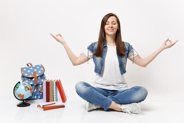 Ritratto di giovane studentessa rilassata con gli occhi chiusi in abiti di jeans meditazione seduto vicino a libri di scuola zaino globo isolati