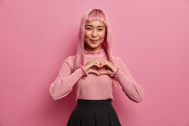 Ritratto di giovane donna asiatica romantica modella il gesto del cuore all'amante, invia affetto e amore, esprime simpatia, indossa una lunga parrucca rosa