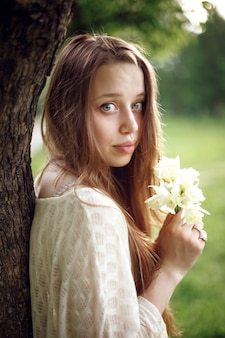 Portrait of young romantic woman with spring flowers, natural beauty