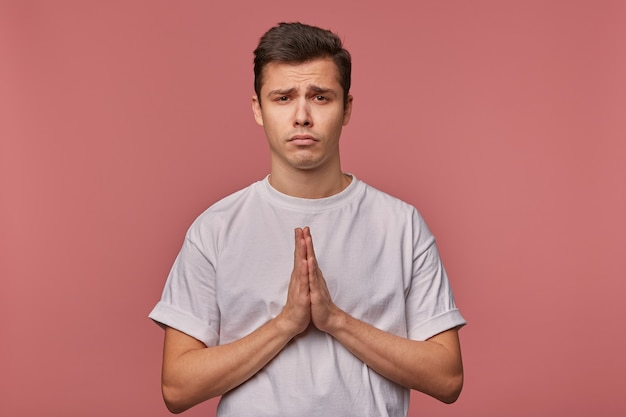 Portrait of young sad guy in blank t-shirt, hopes for luck and shows prayer gesture, stands on pink with unhappy expression.