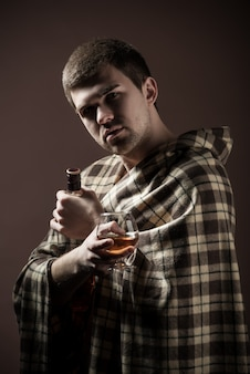 Portrait of a young sad man suffering from alcoholism wrapped up in a plaid with a glass and an alcoholic bottle in his hands against a dark wall